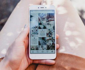 ひざ元で操作される白いスマートフォンのある風景