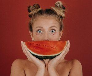 人_半月に切ったスイカを口元にあて、目を見開いて驚きの表情をする女性
