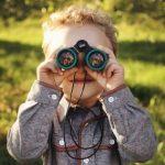 緑の縁取りの双眼鏡をつかって、こちらを微笑みながらのぞき込む小さな男の子