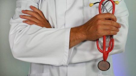 聴診器を右手にもって腕組みをしている男性ドクターの画像