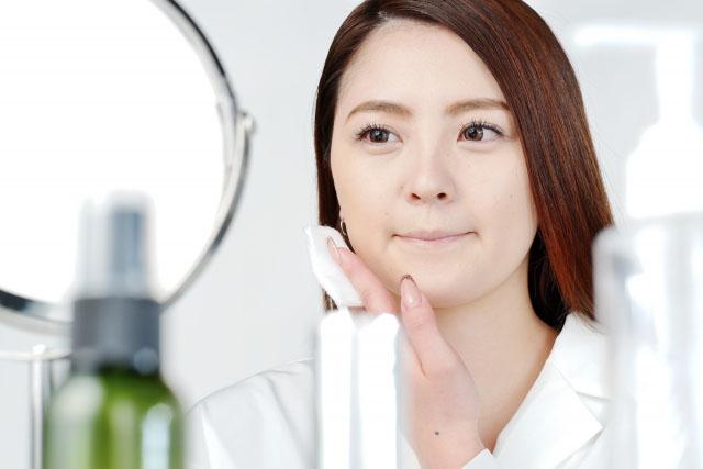 鏡の前でコットンを使ってフェイススキンケアをする女性の画像