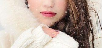白いコートと手袋をして、雪の中で凍える女性