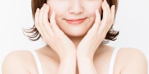 人_顔の横に両手を添えた目をつぶった女性の画像1