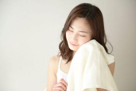 タオルを頬に当てて目をつむる女性