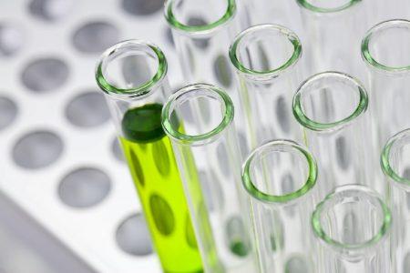 緑の薬品の入った試験管と空の試験管